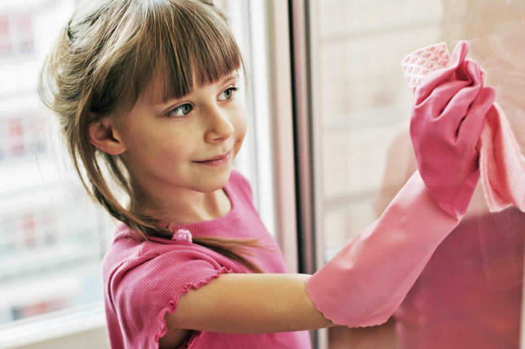 cô bé đang mang bao tay dùng khăn để lau cửa kính