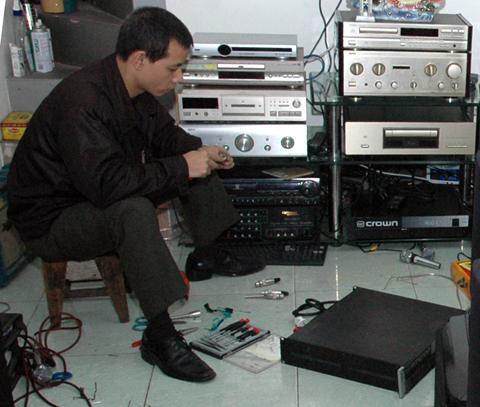 người đàn ông đang ngồi sửa điện