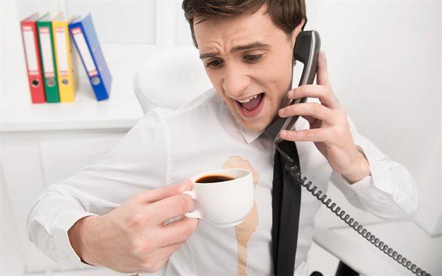 người đàn ông đang nghe điện thoại và đang cáu giận vì cà phê đô lên người