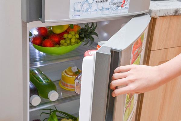 một người đang mở cửa tủ lạnh