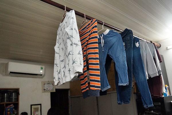Sào đồ đang treo vô số đồ: áo sweater, hoodie, quần, ... sát trần nhà