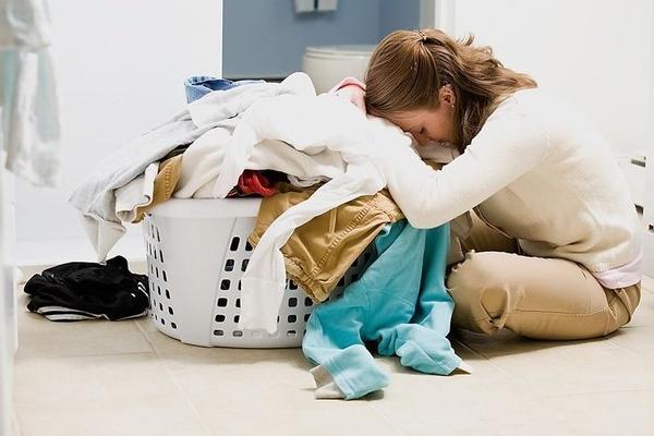 Cô gái đang cảm thấy mệt mỏi bên đóng đồ cần đem đi giặt